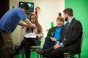 image of Andy sitting down with a man and a women in an interview setting for television