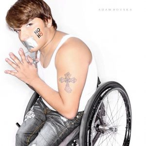 image og Andy sitting in his wheelchair with is hands together, tape over mouth, and NO H8 painted on his cheek