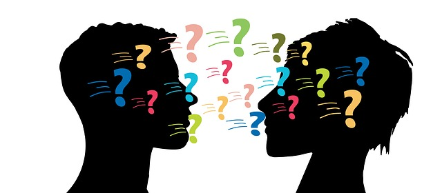 Two silhouettes or people facing each other and colorful question marks being passed back and forth