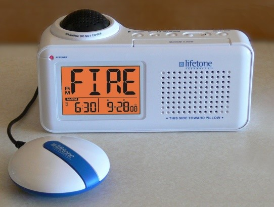 A fire alarm with a large display and speaker. There is a button attached that will vibrate with an alarm.