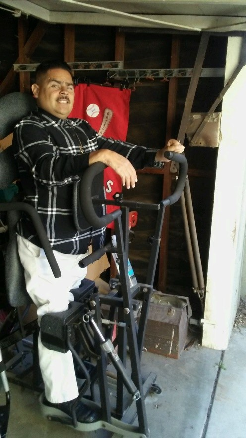 A man is using an adapted device to help him to stand.