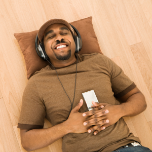 Man of color laying on wood floor with brown pillow, smiling with eyes closed, wearing brown hat and shirt. Wearing headphones and holding a player.