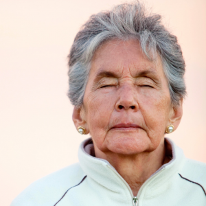 Elder woman in a track jacket with her eyes closed.