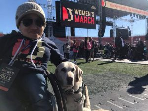 Photo of Mia, woman of Asian heritage wearing sunglasses and a beanie, seated in her wheelchair with service dog Ari by her side at the Women's March in Washington.