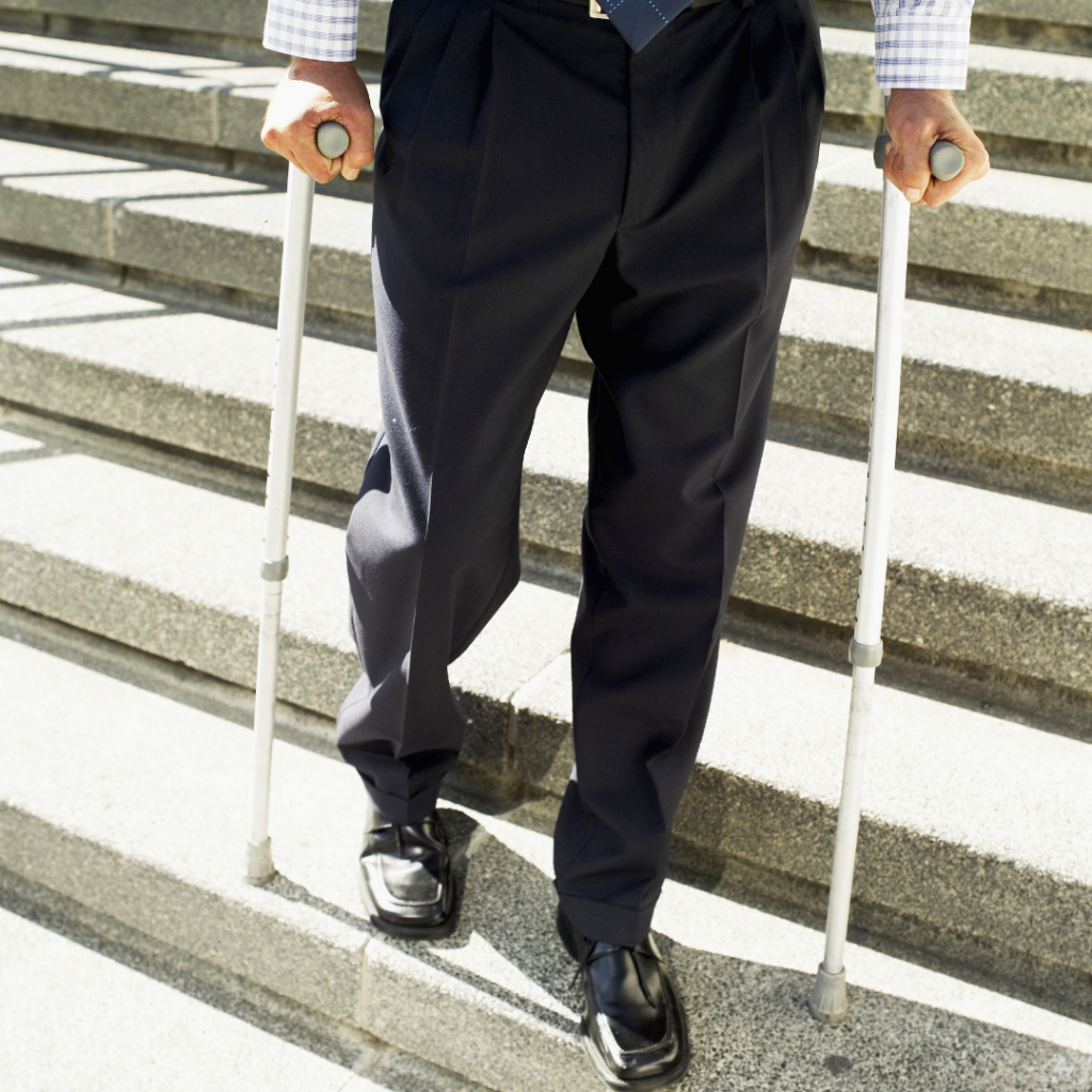 Man in business suit walking with crutches.