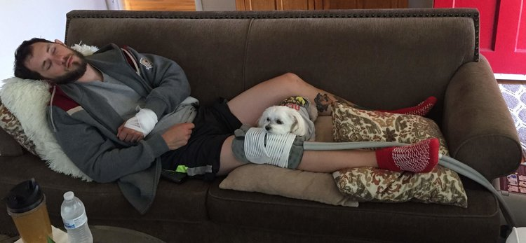 White male with beard, laying on couch asleep with a small white dog laying on his knee, which is wrapped with medical equipment.