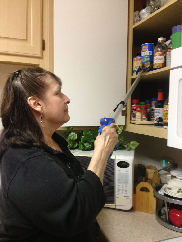 Woman using reacher/grabber tool to get item in kitchen cupboard.