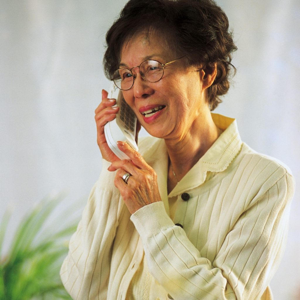 Indoor photo of an elder Asian woman on a landline telephone wearing eyeglasses and a beige cardigan. smiling.