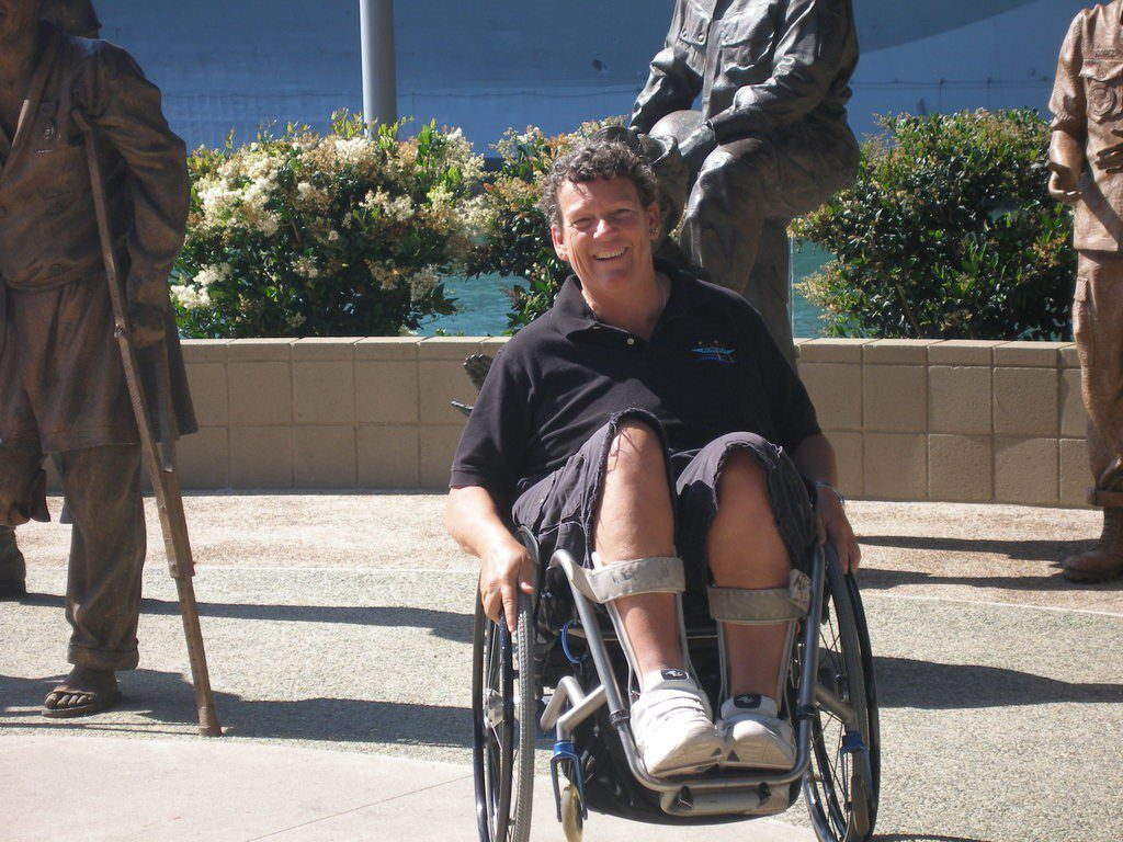 Photo of Angela Madsen in her wheelchair at a disabled veteran monument.