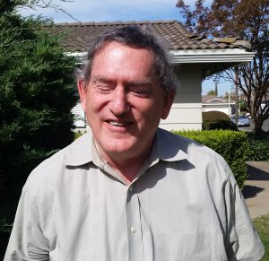 Outdoor photo of an elder white man wearing a collared shirt, smiling.