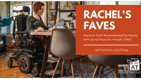 Photo of white woman with curly red hair in a power wheelchair at a desk using a laptop.