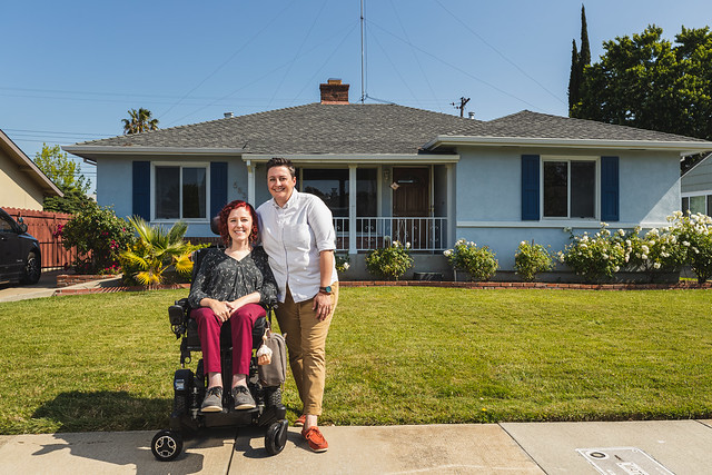 Photo of red haired white woman in a wheelchair wearing a floral top and burgundy pants with a short haired white woman wearing an oxford shirt and khaki pants standing next to her with her arm around her. They are standing in front of a 1950s style one story blue house.
