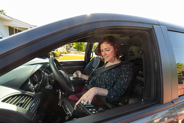 Photo of a white woman smiling in the driver seat of an adapted van pressing buttons on the console.
