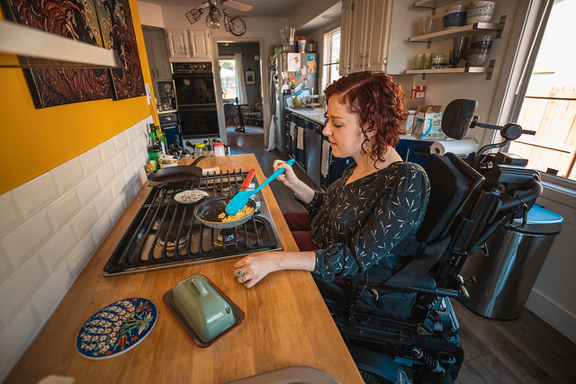 White woman in a wheelchair cooking eggs on the stovetop that she is able to roll under.