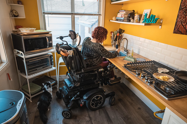 Photo of a woman in a wheelchair washing dishes in a sink that she is able to roll under.