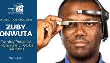 Black man with a visor device wearing a blue collared shirt and v-neck knitted sweater. Text: Spotlight on innovator Zuby Onwuta: Turning Personal Problem into Global Solutions. Where It's AT logo. #BHM2020