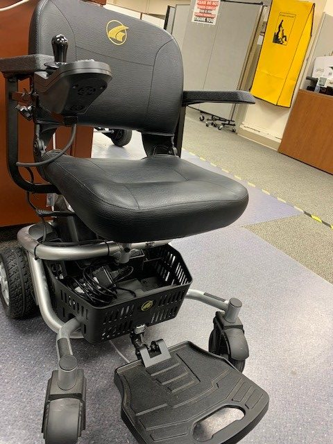 A LiteRider Envy Electric wheelchair in an office filled with desks and cubicle dividers.