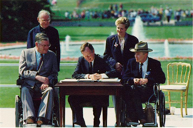 Five people at a table outdoors, signing a document.