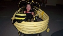 picture of a litle firl in a bee costume and her wheelchair is a honeycomb