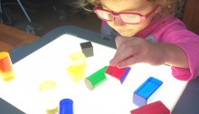 Olivia using her light box wearing pink glasses and looking at different colors and shpaes of blocks on the box