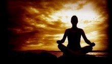 picture of a woman sitting cross-legged in a meditation pose with the sun setting