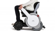 picture of the WHILL - a white futuristic and modern looking wheelshir with a woman pushing down the arm