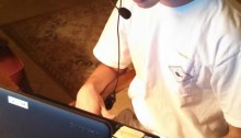 picture of a young causcasian man with brown hari sitting at a desk with a headset and laptop on