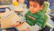 Picture of a little boy sitting at a desk using a communicaiton tablet