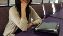 Picture of Haley Dayel sitting at a table with a communication device in front of her