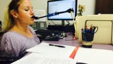 Kim at her desk using the mouth grabber to write with a pen
