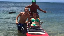 kim on the paddleboard in the ocean with ron and her friend next to her