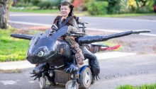 picture of young boy and his wheelchair is an elaborate flying froglike creature he is smiling