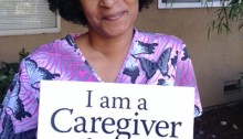 picture of a smiling woman seated and holding a placard that says I am a caregiver for my mom
