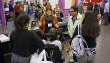 Picture of Ability Tools staff member speaking to a family about assistive technology at the Abilities Expo