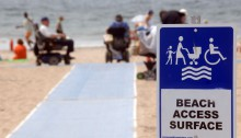 Beach accessibility sign with long beach path in backgroud and a wheelchair user using the path