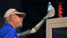 Arte McAuley using his arm to reach and grab a water bottle off the top of a cabinet