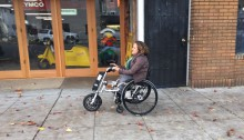 Women in wheelchair with firefly attached to the front zooming past a store front