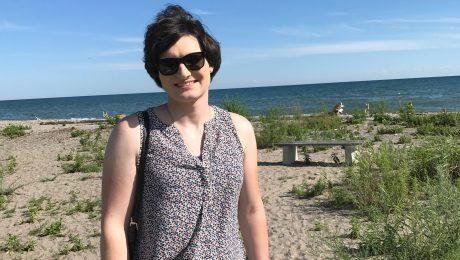 Women standing on the beach while wearing dark sunglasses