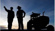 the silhouettes of two farmers standing next to a tractor