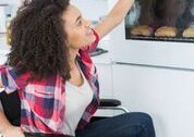 A woman of color is sitting in her wheelchair opening a wall oven.