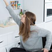 A woman with long hair using a wheelchair is accessing her pull down kitchen shelf.