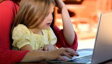 A young girl sits on her mom's lap looking at a laptop together.