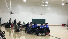 A team of wheelchair rugby players wearing blue are huddled together.