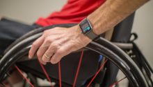 The torso of a man sitting in a wheelchair is shown, he is using the Apple watch wheelchair workout
