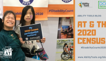 "A woman in a power wheelchair smiling with an adolescent child by her side. The child is holding a sign that reads, ""My 2020 Census participation matters!"""